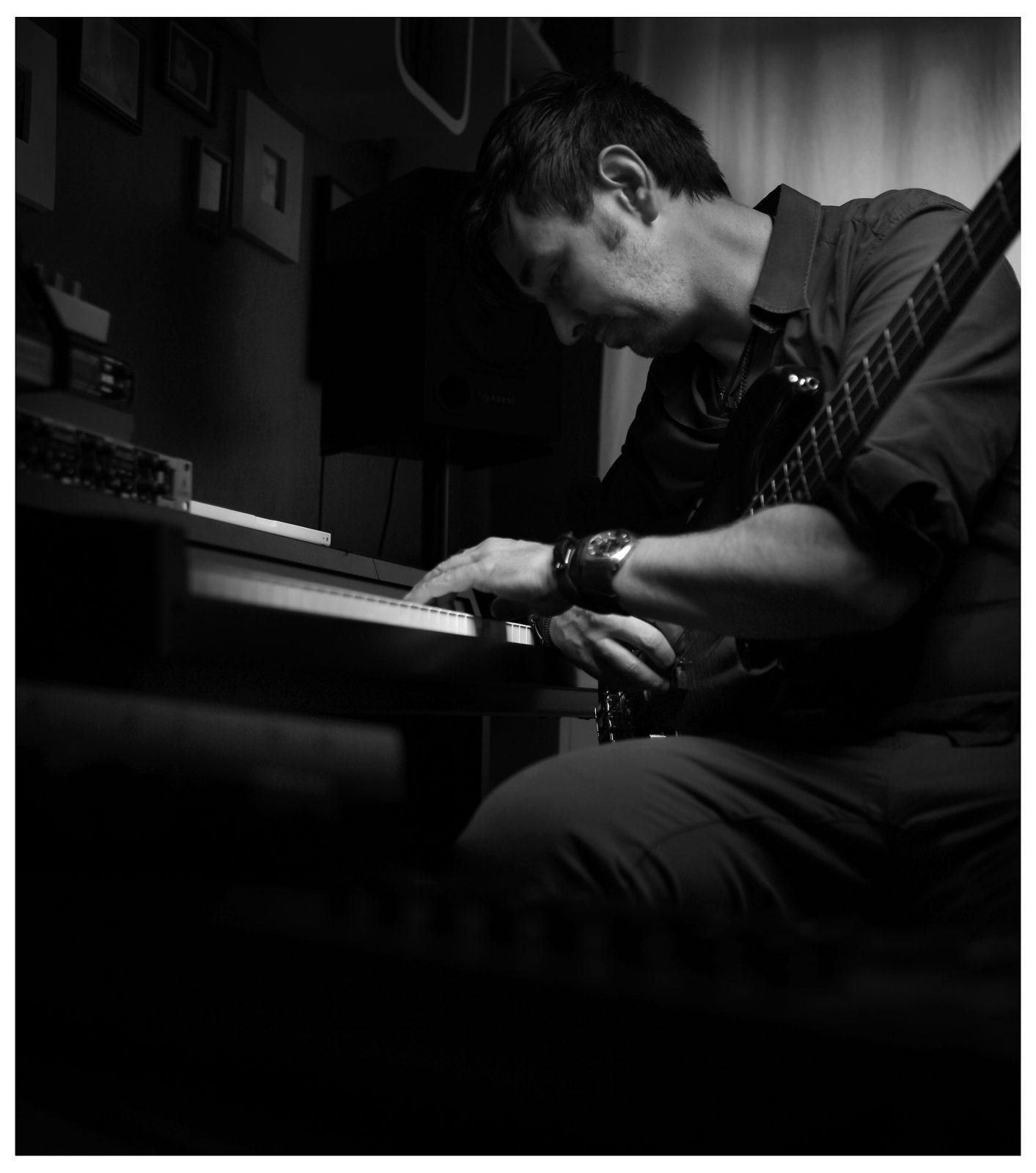 The musician David Alleckna of Hamburg sitting in his studio, working on a production, sitting by his keyboard, having his bass on his lab.